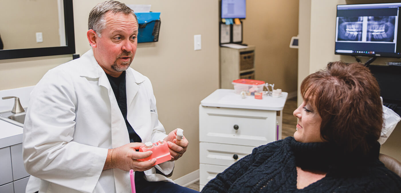 Doctor Owens showing patient a dental implant model